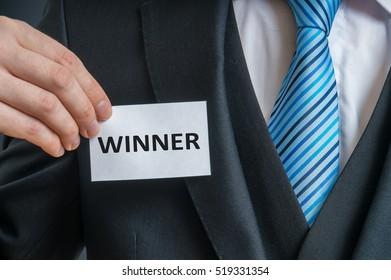 Man in suit is showing label that He is a winner.