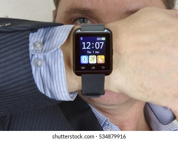 man in a suit shows a smart watch and looking at the camera