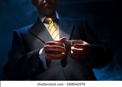 The man in a suit shuffles cards, in his sleeve he has a diamond ace
