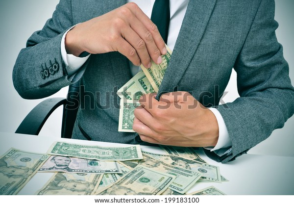 man in suit sitting in a desk full of dollar bills getting them in his jacket