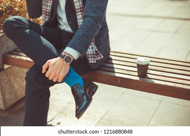 Man in suit is sitting on bench with crossed legs, showing his blue socks and a beautiful watch, while having a coffee cup near him