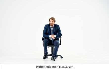 a man in a suit is sitting on a chair
