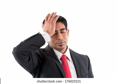 A man in a suit slapping himself in the forehead.