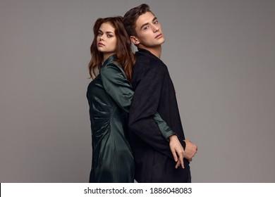 Ein Mann in einem Anzug steht mit dem Rücken zu einer Frau in einem Kleid auf grauem Hintergrund und hält Hände