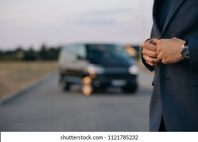 Man in suit stay in front of luxury car minivan