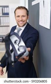 Man in suit stretching out virtual reality glasses towards camera and smiling, standing in office interior