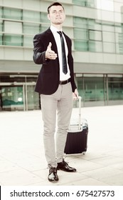 Man in suit with suitcase is meeting his partner in another city.