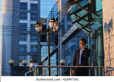 Man in suit talking on mobile phone against the building with a glass facade