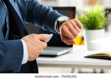 Man in suit and tie check out time at silver wristwatch closeup. Show and point with finger waste minute modern punctual life style start hurry job idea last second clockwork precision concept