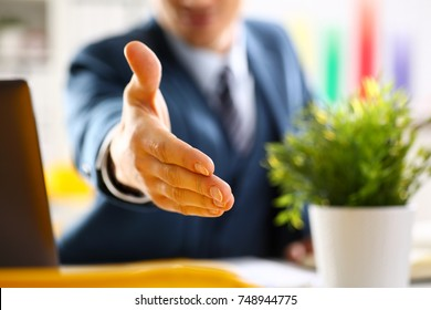 Man in suit and tie give hand as hello in office closeup. Friend welcome mediation offer positive introduction thanks gesture summit participate approval motivation male arm strike bargain