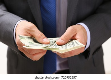 Man in suit and tie hold in arm pack of hundred dollar bills closeup.