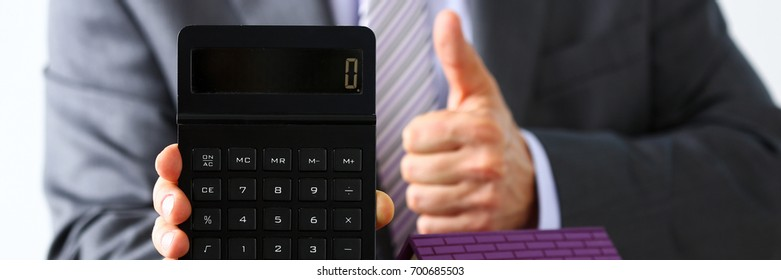 Man in suit and tie hold in arms calculator with little toy house closeup. New owner or tenant, percent rate, sell or rental structure, seller deal, family solution, pledge negotiation, industry