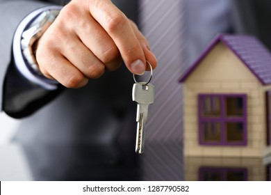 Man in suit and tie hold in hand silver key giving it to buyer closeup. New owner pledge idea for life family solution male arm credit negotiation clerk in office future plan concept