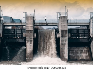 Man in suit and tie standing on top of a private small size hydro central dam that can power 20000 households with electricity.