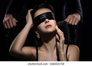 Man in suit ties a woman's eyes with a silk ribbon on black back