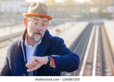 man in suit at train station looking annoyed at his wristwatch