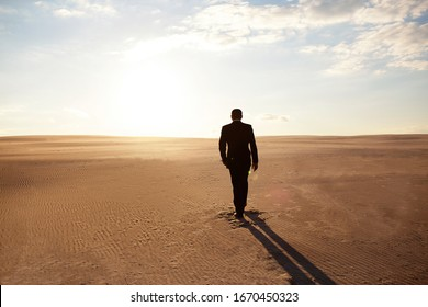 A man in a suit walks through the desert, loneliness, pursuit of his goal, the hot sun, a man lost in the desert, a businessman at the beginning of his journey, forward movement, willpower