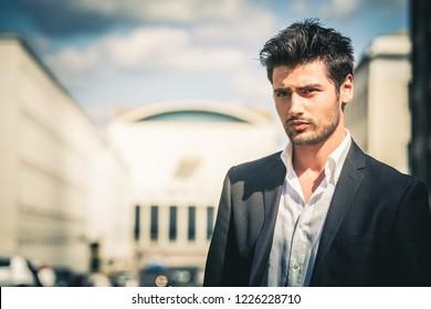 Mann in Anzug und weißes Hemd aussehen. Mit modischem Haar und Bart. Draußen auf der Straße in der Stadt. Himmel und Gebäude im Hintergrund.