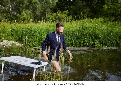A man in a suit, but without pants, leaves a workplace located in a river ecosystem in the wild. A businessman steps knee-deep in the water, leaving behind a desk with a laptop and a phone.