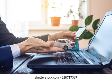 The man in the suit working in the office at a laptop, holding a car paying with a credit card. The concept of finding and buying cars on the Internet