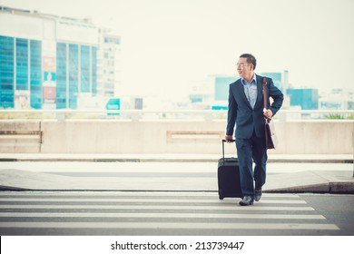 Man with a suitcase crossing the road to leave the airport