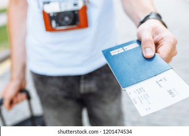 A man with a suitcase, holding a passport and tickets close-up