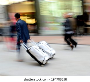 Man with suitcase in a hurry. Intentional motion blur