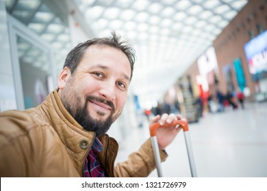 Man with suitcase on airport taking selfie