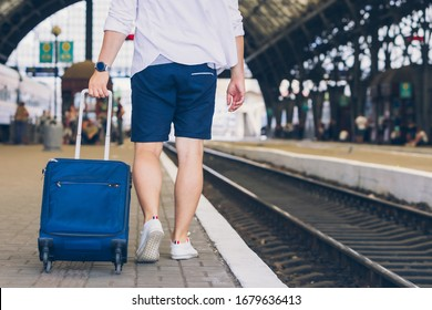 man with suitcase on wheels walking by railway station platform