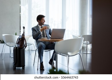 Man with suitcase sitting in airport waiting area. Business man sitting at airport lounge with laptop having coffee and looking away.