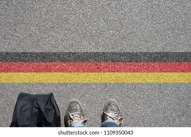 A man with a suitcase is standing at the German border