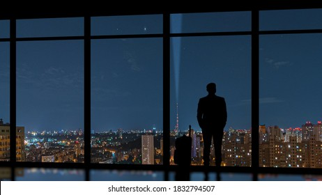 The man with a suitcase standing near a panoramic window against an evening city