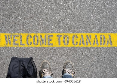 A man with the suitcase stands on the border with Canada