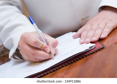 man in suite signing paper