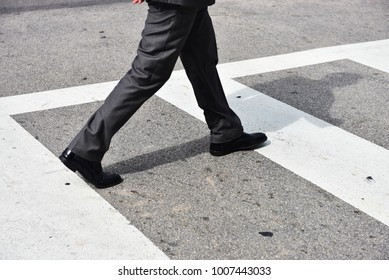 Man in suite walking in the street passing the zebra