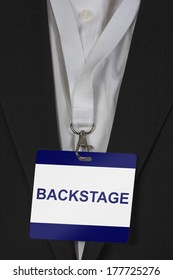 man in suite wearing a Backstage pass arround his neck