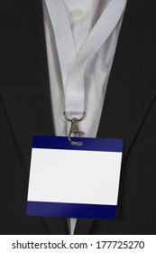 man in suite wearing a blank pass card arround his neck