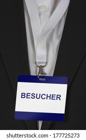 "man in suite wearing a pass labeled ""Besucher"" (German Visitor) arround his neck"