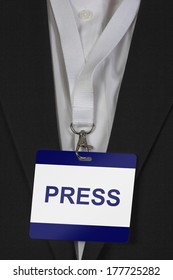 man in suite wearing a Press pass arround his neck