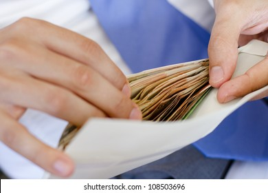 Man in suits is counting how much money in an envelope