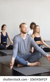 Man in Sukhasana pose, group of young sporty people practicing yoga lesson, doing Padmasana exercise, Lotus pose, working out, indoor full length, students training in sport club, studio
