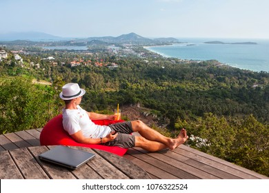 Man is summer clothes businessman sitting with amazing island Samui view place, hold cocktail and phone in hand, outdoors. Relax after freelance work. Near closed laptop, pause for enjoy landscape
