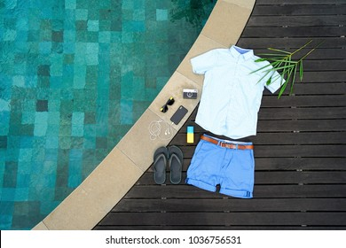 Man summer clothes collage flat lay isolated on dark wood background with swimming pool. Summer outfit of casual man desk top view fashion accessories: shirt, shorts, sunglasses, camera, smartphone