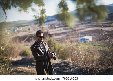 Man with sun glasses waking with camera in nature