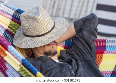 man with sun hat relaxing in a hammock at sunset