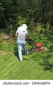 A man in a sun protective hat pushes a lawn mower in an endless attempt to tame the surrounding jungle of vegetation