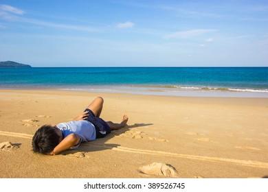 The man sunbathing on the beach.