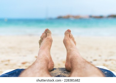 Man sunbathing on lounger. Legs.