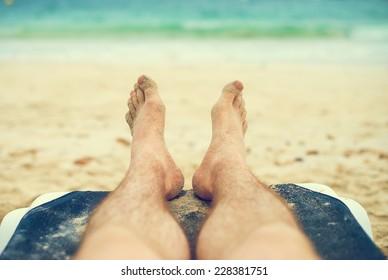 Man sunbathing on lounger. Legs. Vintage effect.
