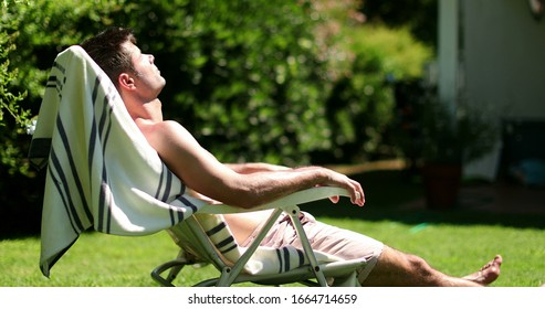 Man sunbathing outside in home lawn. Person outdoors relaxing